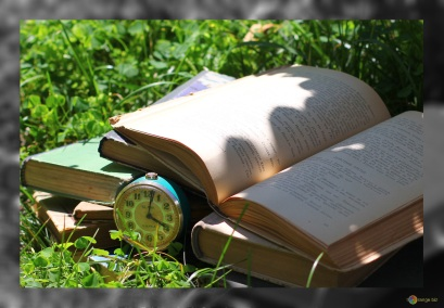books and clock on grass